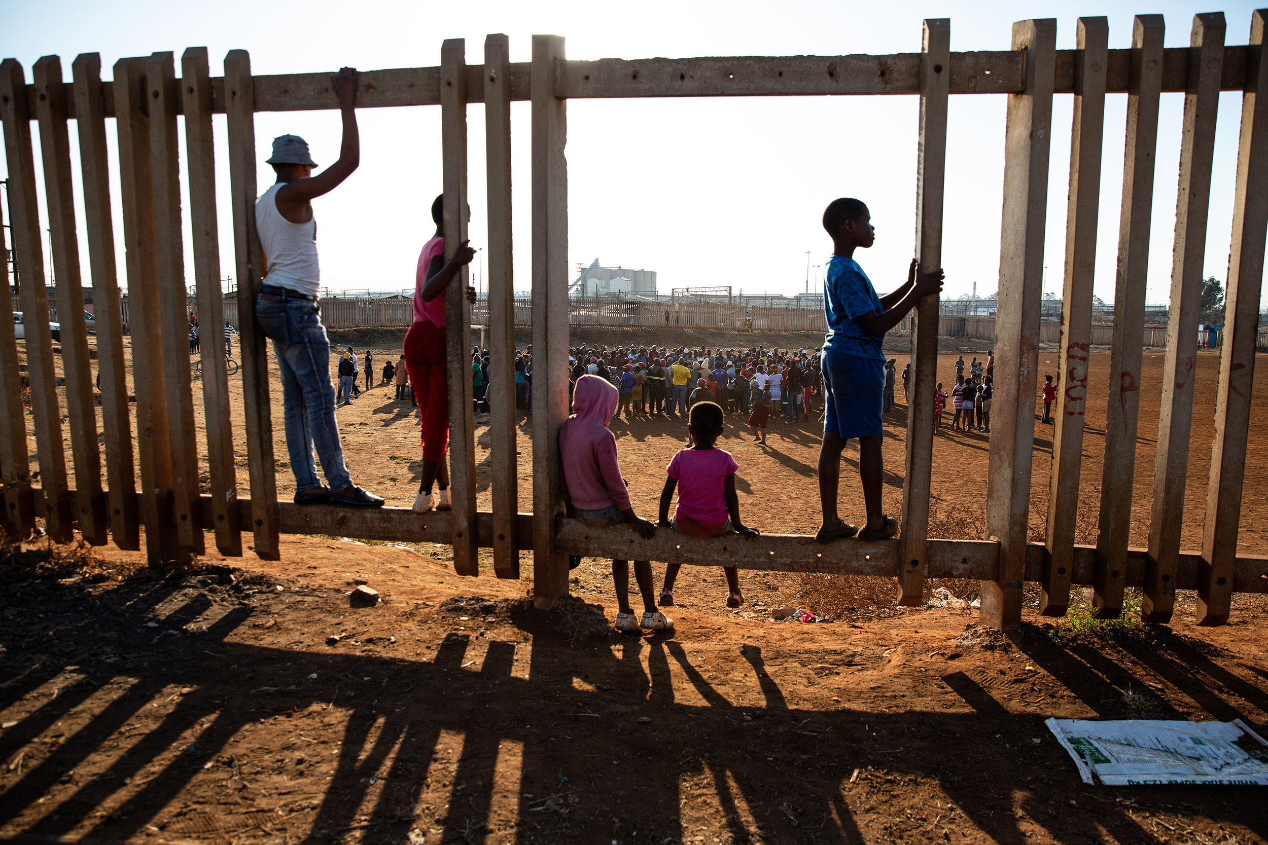 7 July 2020: Children watch the meeting taking place at a football field in Thokoza. A group of men marched in the township after taking part in the trucker's strike. Xenophobic speech and threats towards migrants from other African countries characterised the protest.