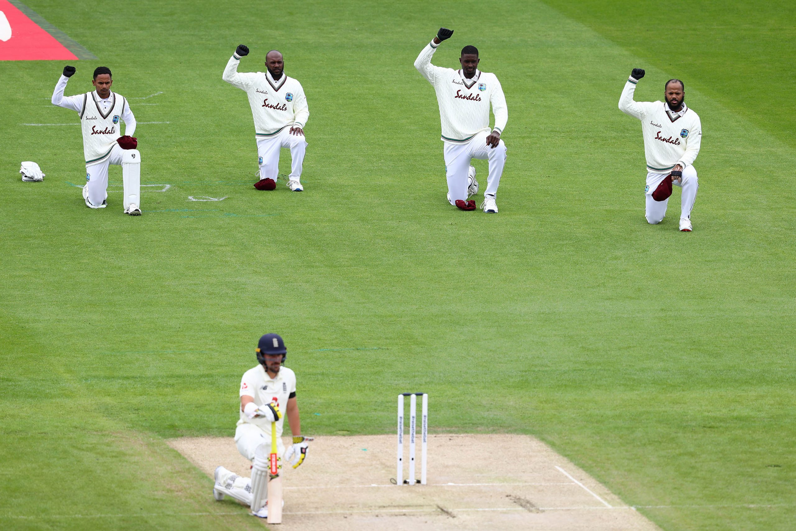 16 July 2020: West Indies cricketers with black gloves on their right hands take a knee in support of the Black Lives Matter movement on day one of the second Test of their #RaiseTheBat series against England at Old Trafford in Manchester, England. (Photograph by Michael Steele/ Getty Images)