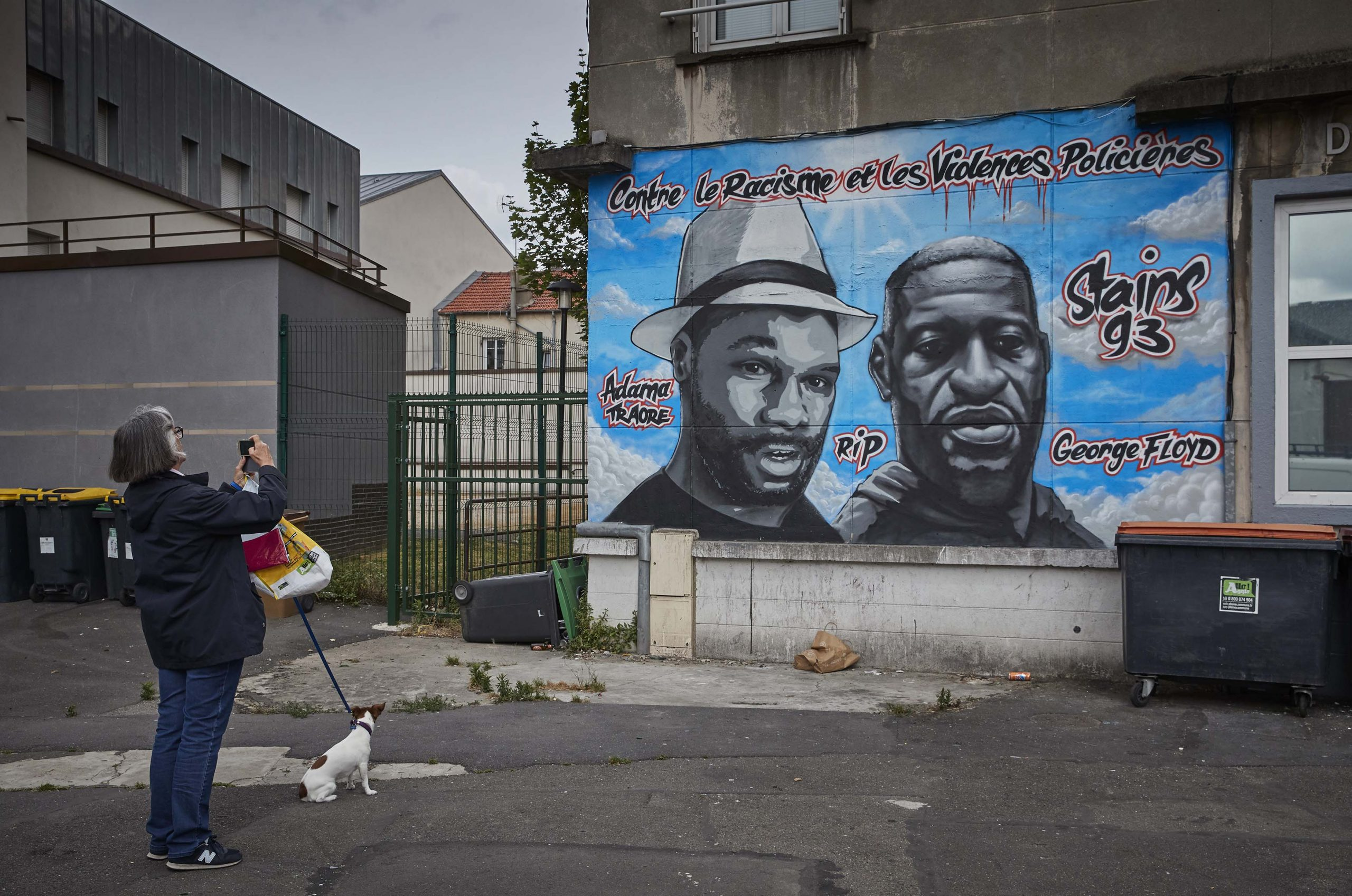 17 June 2020: A woman walking her dog photographs street art paying tribute to murdered American George Floyd (right) and Malian Frenchman Adama Traoré (left) in the Parisian suburb of Stains in Paris, France. (Photograph by Kiran Ridley/ Getty Images)