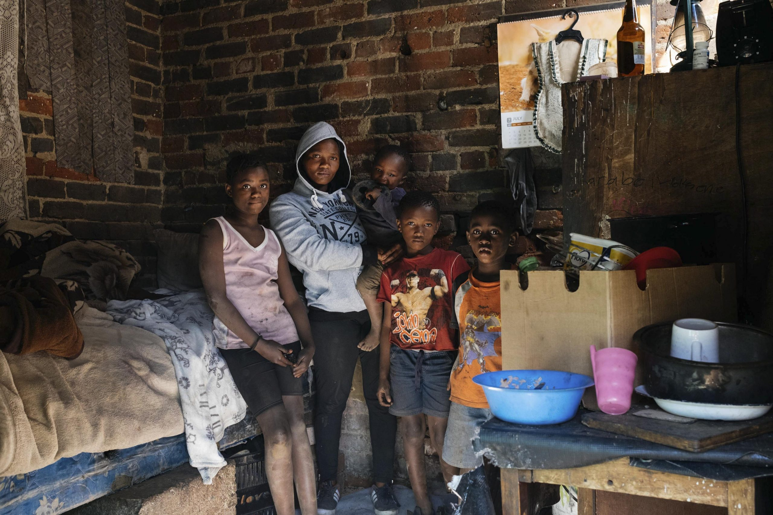 16 July 2020: Mpho Mokoena, 28, with her children, from left, Karabo, Kgotso, Kutlwana and Thumelo in their single-room apartment in Johannesburg's inner city. Mokoena shares the single bed with her boyfriend and the children sleep on the floor. Their building has no running water or toilets, making regular hand washing and general hygiene challenging.