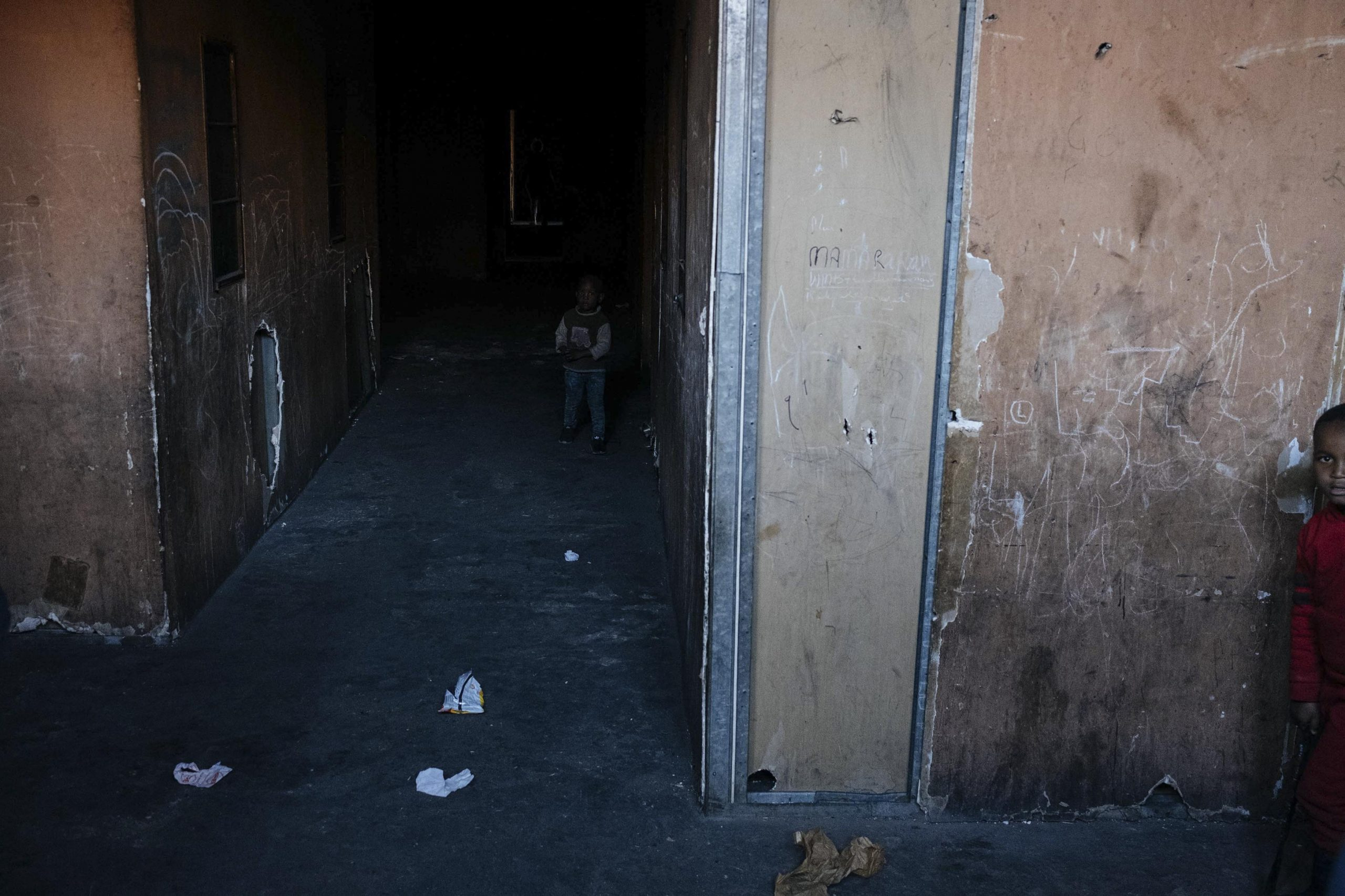 16 July 2020: Children play in the corridor of an inner-city building. Characterised by dark passageways because of the lack of electricity, derelict buildings such as this one are vulnerable to outbreaks of fire as residents rely heavily on paraffin for cooking and warmth. Those inhabiting these spaces are often living at the extremes of urban existence, where rent is affordable but conditions are crowded, cramped, dangerous and insecure.