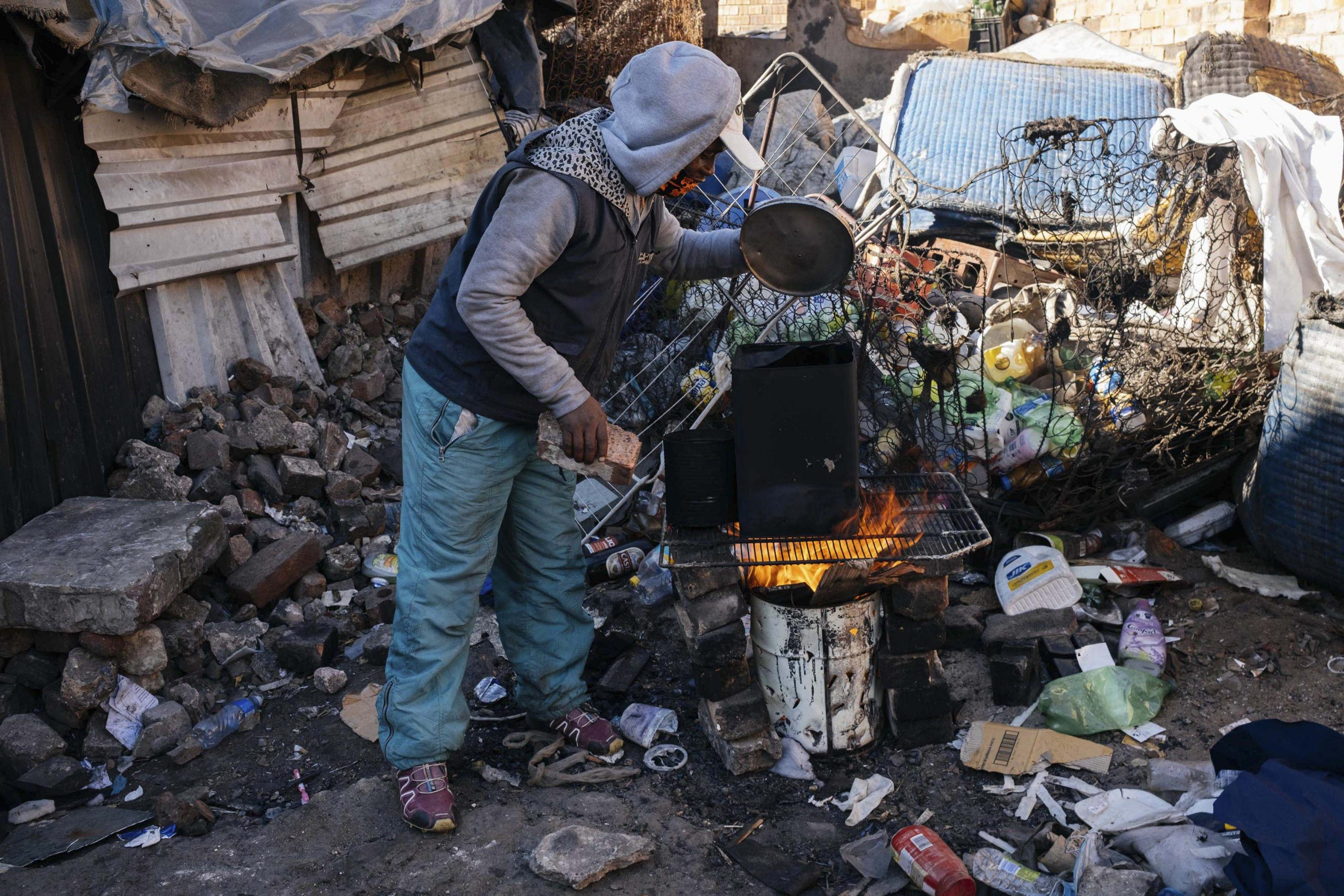 16 July 2020: Ramaketse Rampaleng, 34, warms himself at a fire at the Gomorrah Building in Johannesburg's inner city. He makes a living working in the city's informal recycling sector, but worries that collecting waste may expose him to the coronavirus. Despite not having access to running water at Gomorrah, which prevents him from regularly washing his hands, he has to keep working to survive.