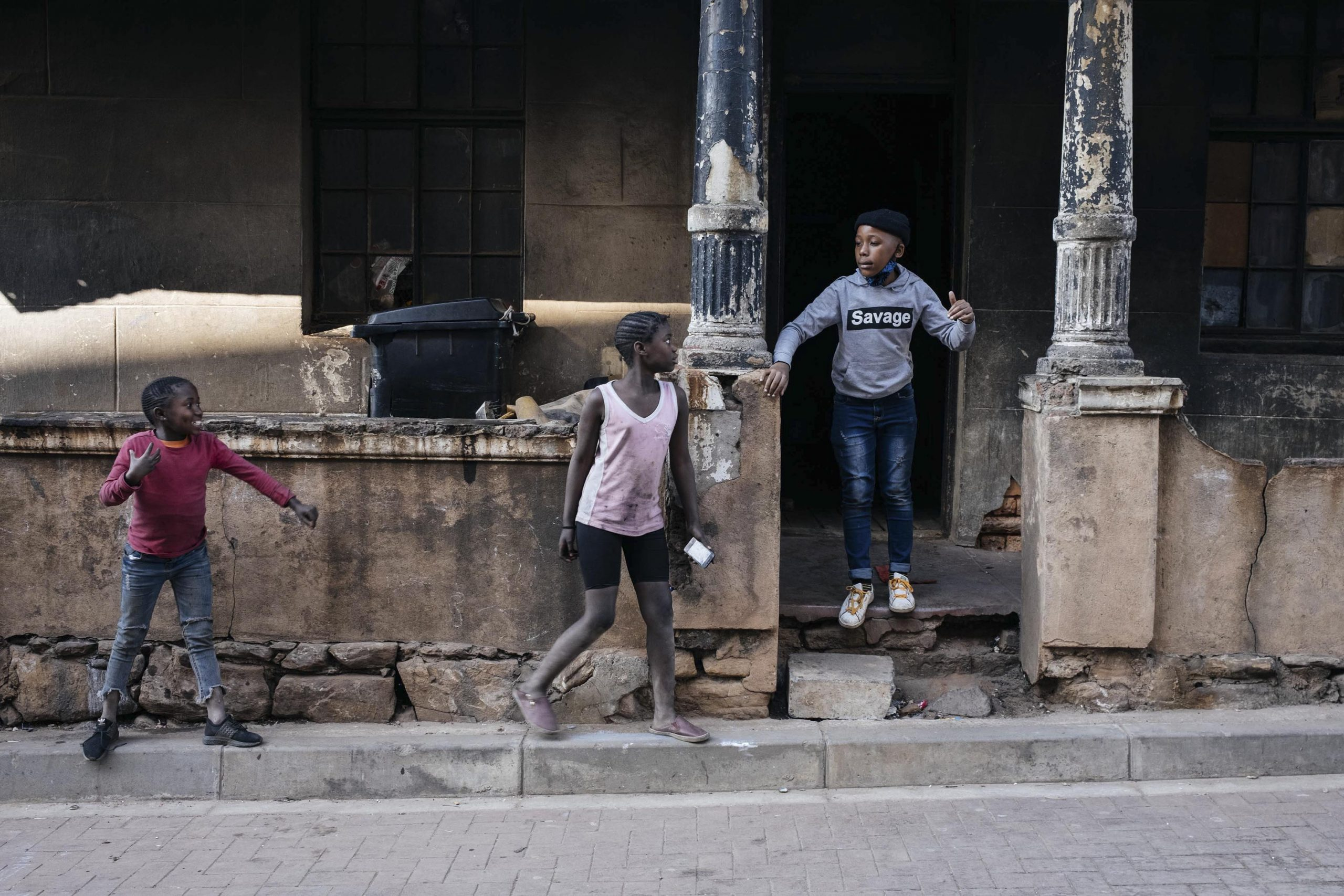 16 July 2020: Karabo Mokoena plays with friends outside the front entrance of the Gomorrah Building, the dilapidated structure without running water, toilets or electricity in Joburg's inner city that is their home.
