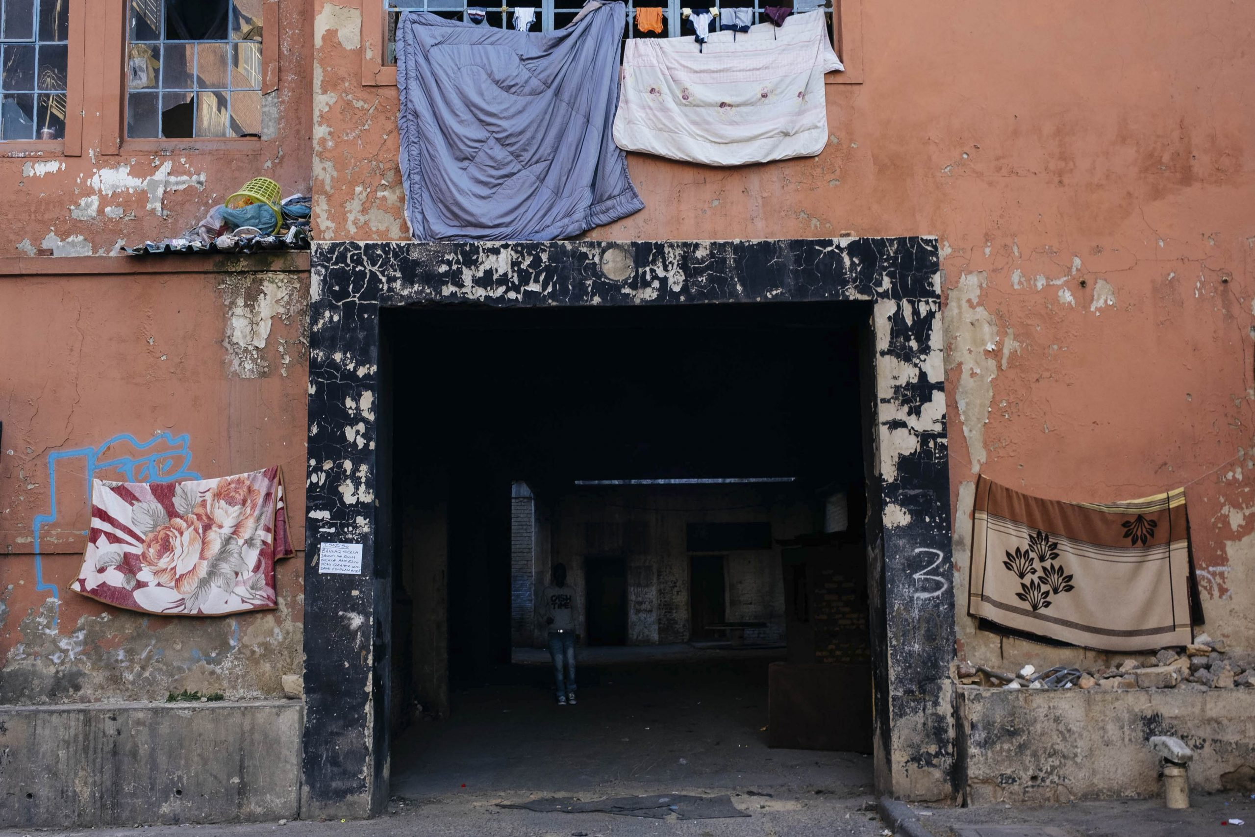 16 July 2020: Blankets hung out to dry at the entrance to the Delvers Building in the inner city. Rent is R200 a month, but there is no electricity or running water and there are no ablutions in the building. Residents have to collect water from a communal tap outside for washing, cleaning and cooking, increasing their vulnerability to coronavirus exposure and making regular hand washing difficult.