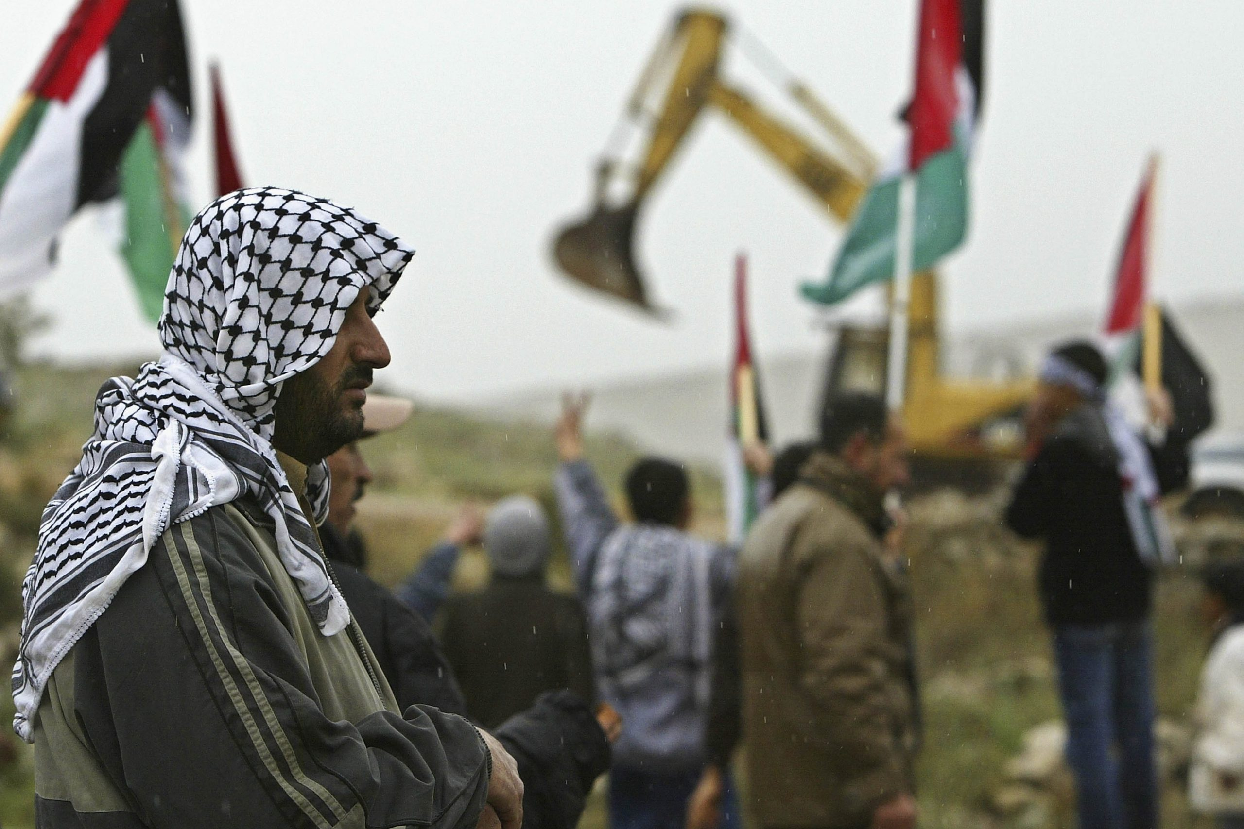 22 January 2004: Palestinian villagers and Israeli and foreign peace activists demonstrate against Israel's security fence being built on land near the West Bank hamlet of Budrus. (Photograph by David Silverman/ Getty Images)