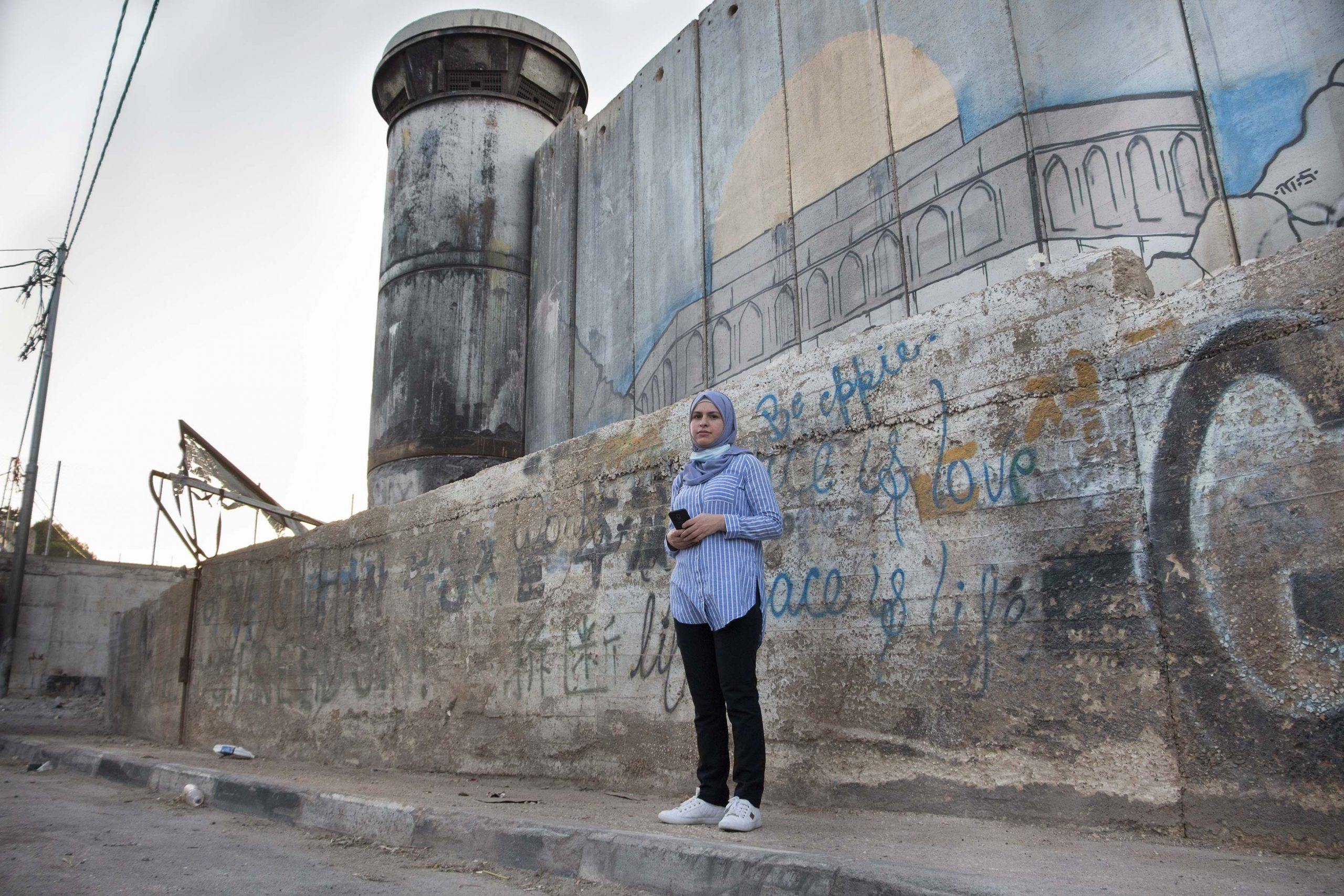 19 July 2020: Iltizam Morrar stands in front of the Israeli military watchtower and giant 'apartheid wall'. Israel has been building the barrier through the West Bank since 2002 to annex the land and divide the region into dozens of disconnected areas. (Photograph by Reem Jarrar)