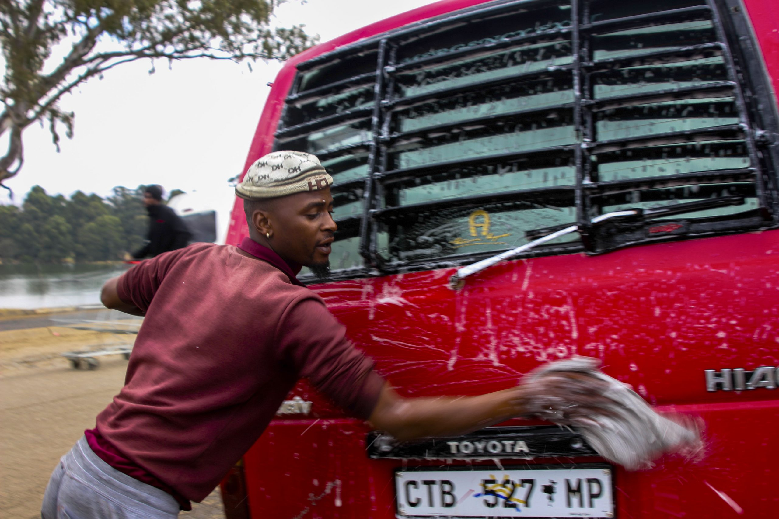8 June 2020: Sibusiso Motha, 26, survives by washing taxis at Mkhondo taxi rank. If the drivers don't make enough money through trips, his job is directly affected as it relies on the taxi operators' cash flow. (Photograph by Magnificent Mndebele)