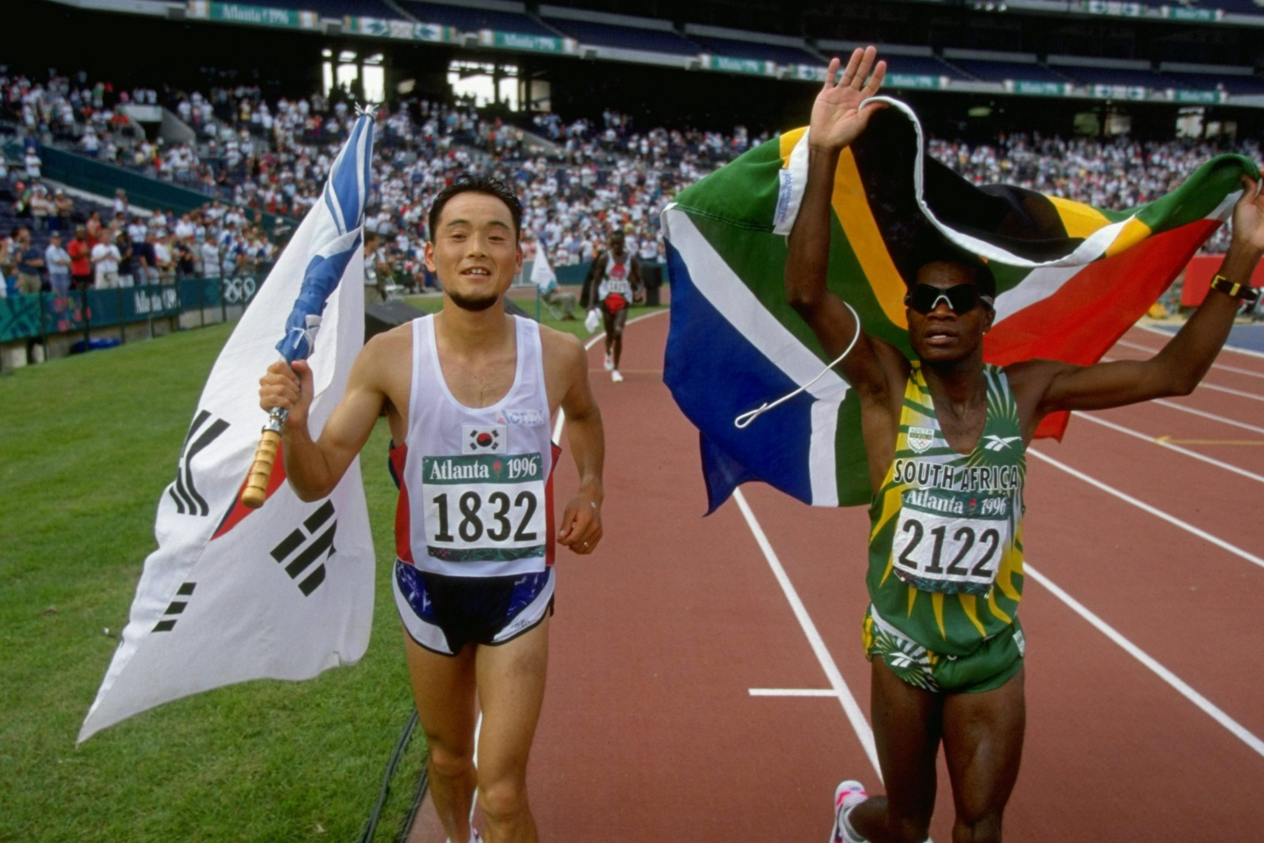 14 Aug 1996: Josia Thugwane celebrates with Bong-Ju Lee of South Korea after the men's marathon at the Summer Olympics in Atlanta, Georgia. Thugwane won gold with Lee taking silver. (Photograph by Mike Powell/ Allsport)