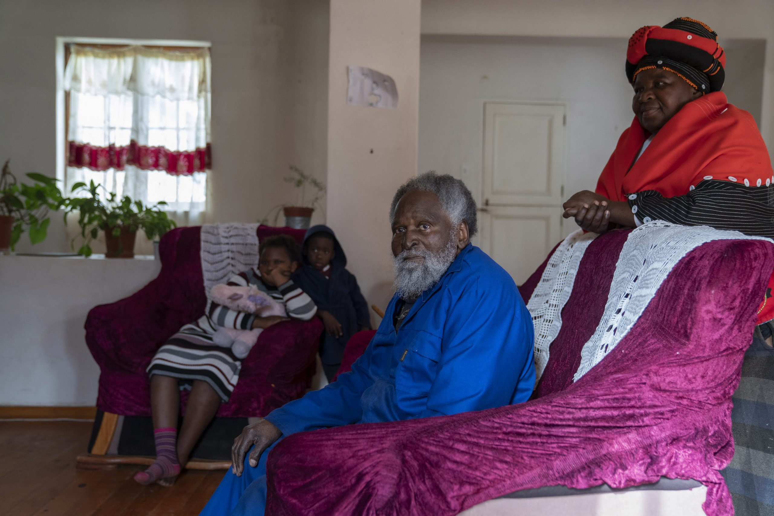 1 July 2019: Lungiswa Madinda stands behind her father Mongezi Madinda in their home on Castle Farm. The family moved to Peddie in the former Ciskei, but returned to the area after a land restitution case was settled in 2006.