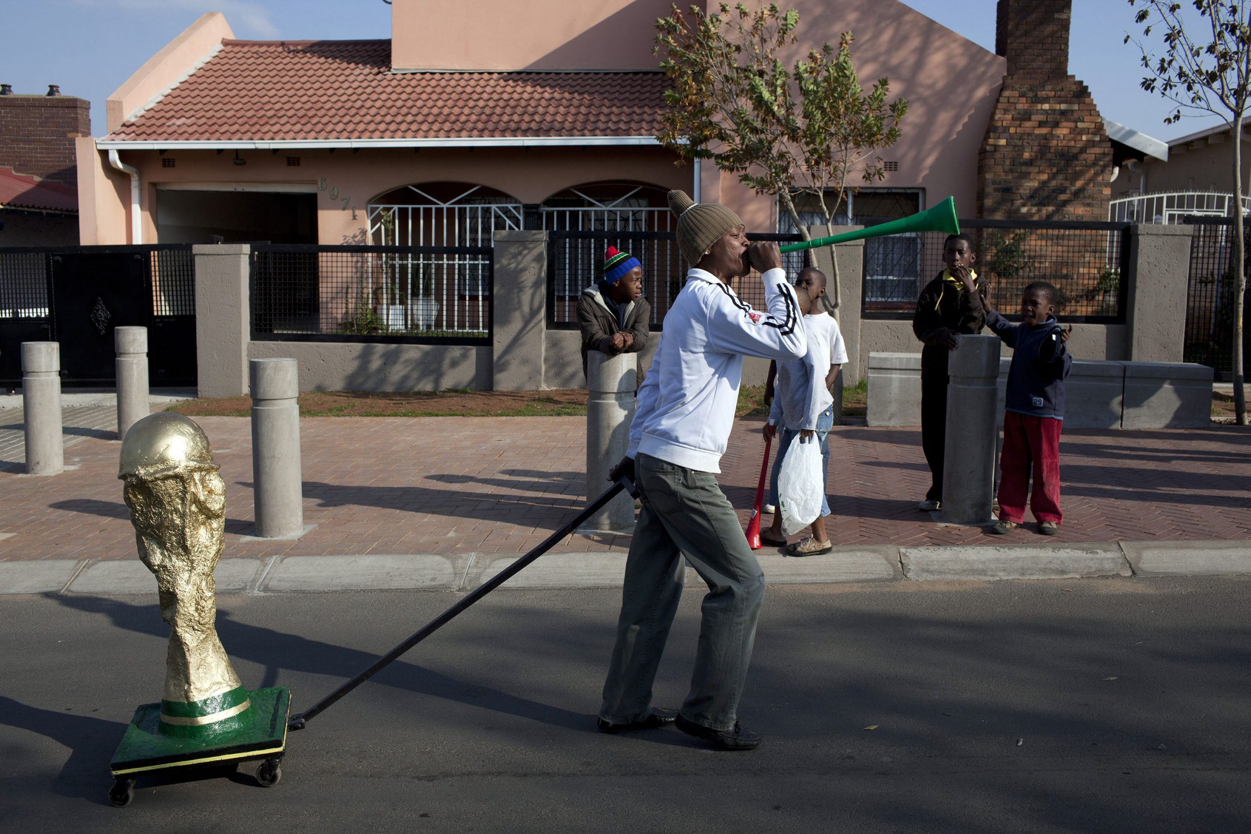 11 June 2010: A man pulls a cart with a homemade Fifa World Cup trophy on Vilakazi Street in Orlando, Soweto, as residents and visitors celebrate in the streets at the start of the tournament. (Photograph by Per-Anders Pettersson/ Getty Images)
