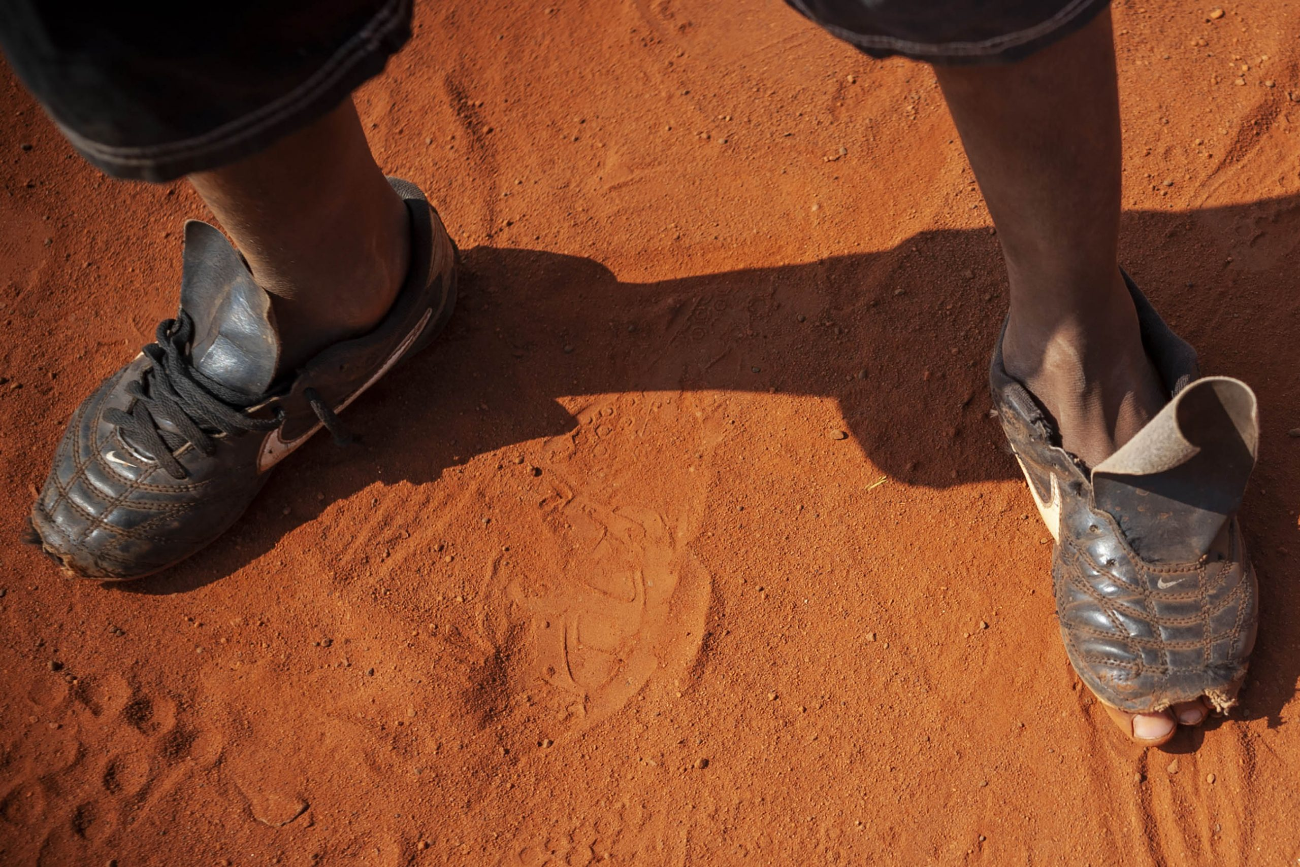7 May 2014: A young Sowetan footballer's toes peek out from his worn football boots as he takes a break during an informal game on a dusty football pitch in Dobsonville, Soweto. (Photograph by Ihsaan Haffejee)