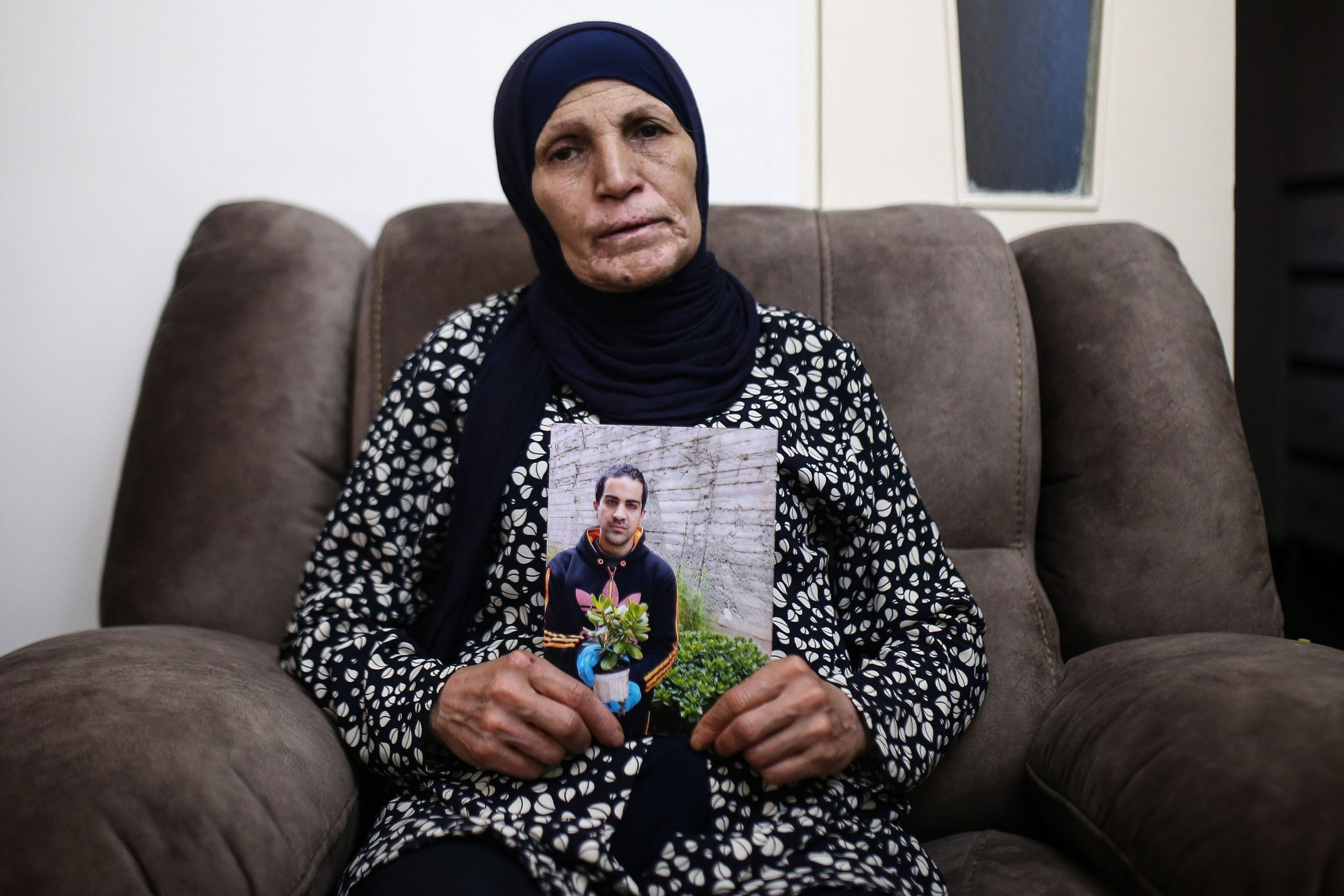 2 June 2020: Rana Hallak holds a photograph of her autistic son Iyad Hallak, 32, who was shot and killed by Israeli police in East Jerusalem's Old City on 30 May. (Photograph by Mostafa Alkharouf/ Anadolu Agency via Getty Images)