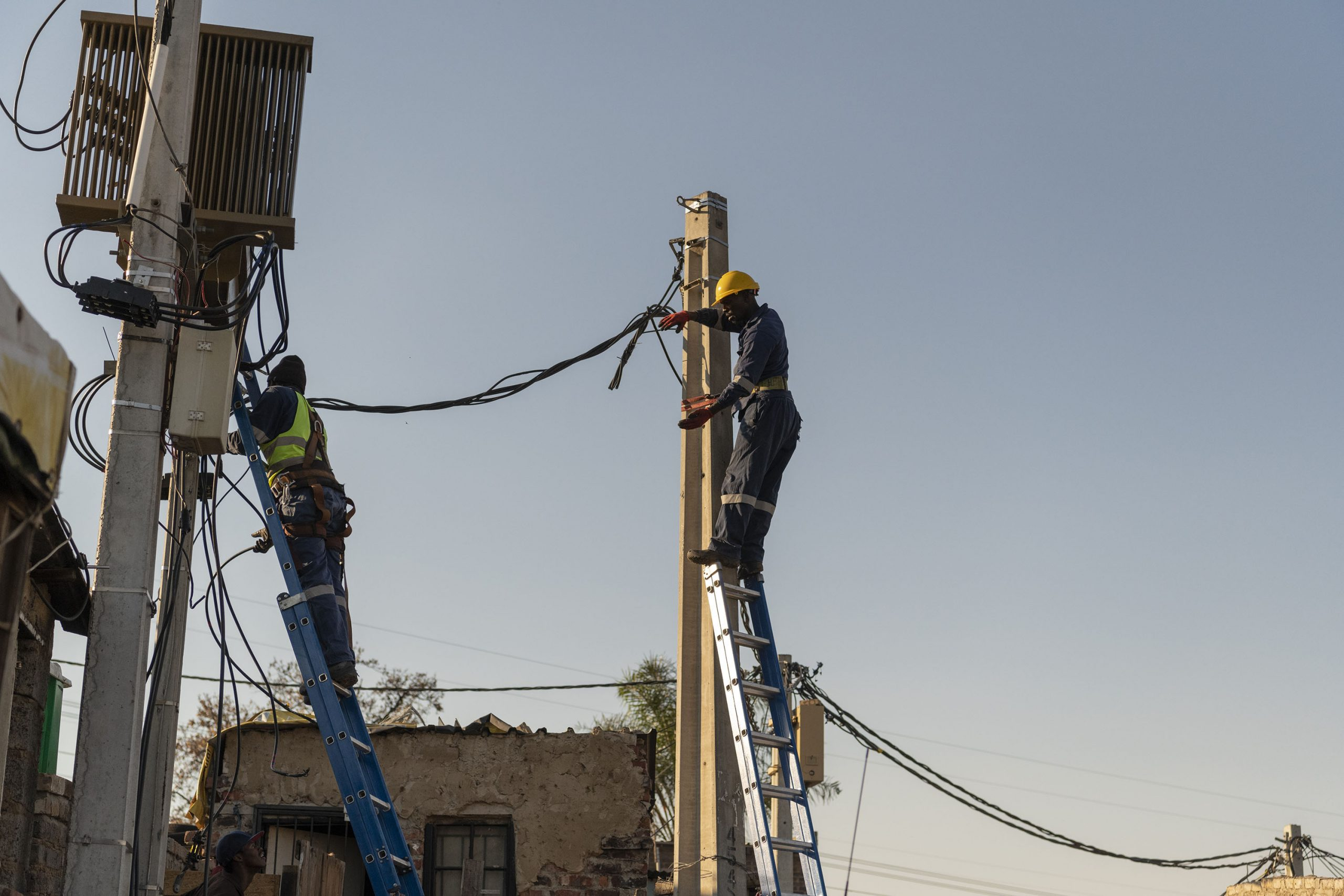 22 June 2020: City workers fix electricity pylons in the densely populated settlement of Stjwetla in Alexandra, Johannesburg. (Photograph by Ihsaan Haffejee)