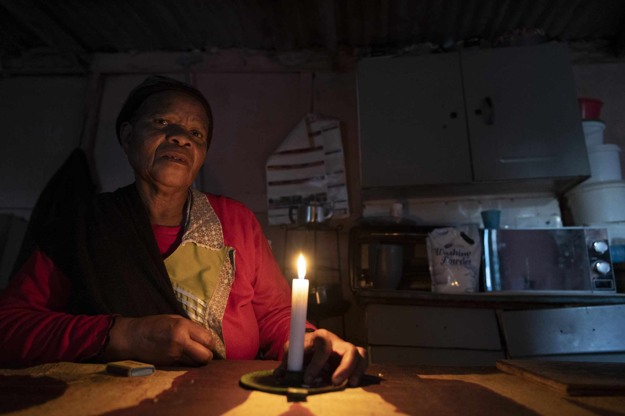 22 June 2020: Thandi Magxotywa inside her shack home in Stjwetla. Electricity supply is erratic and she has to make use of candles for light and a paraffin stove for warmth in winter. (Photograph by Ihsaan Haffejee)