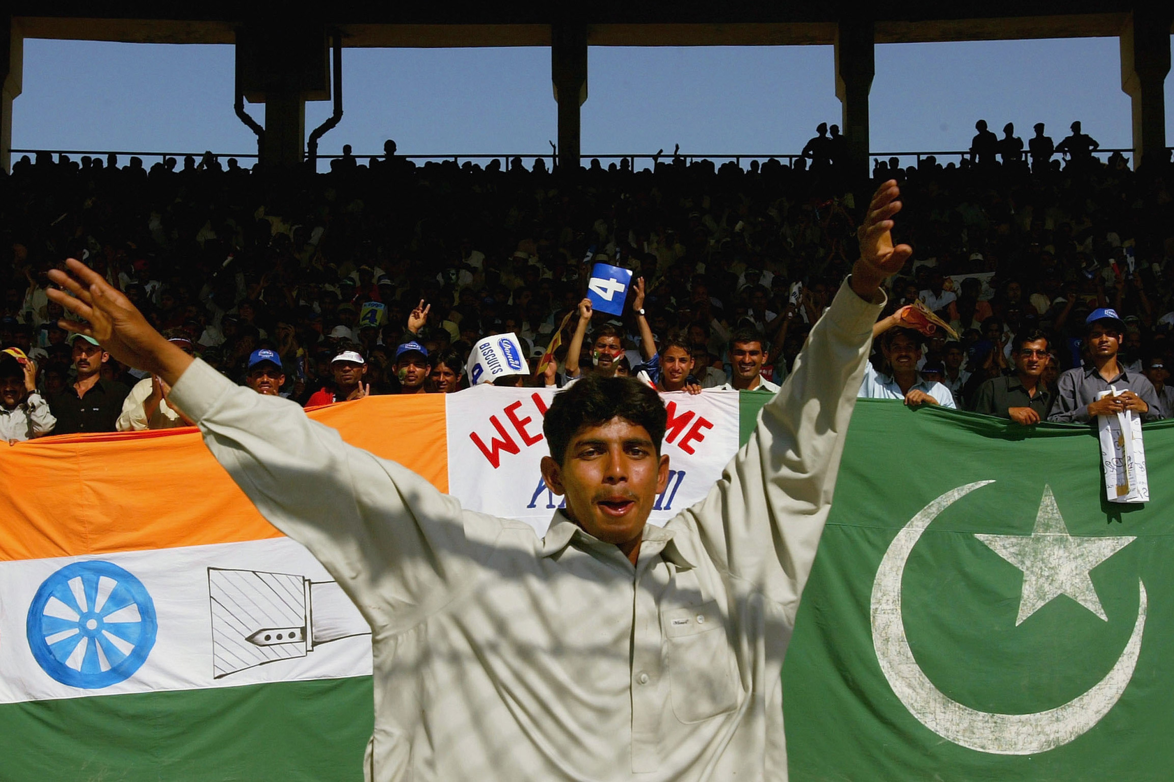 13 March 2004: Cricket fans celebrate India's first one-day international against Pakistan at the National Stadium in Karachi, Pakistan. (Photograph by Scott Barbour/ Getty Images)