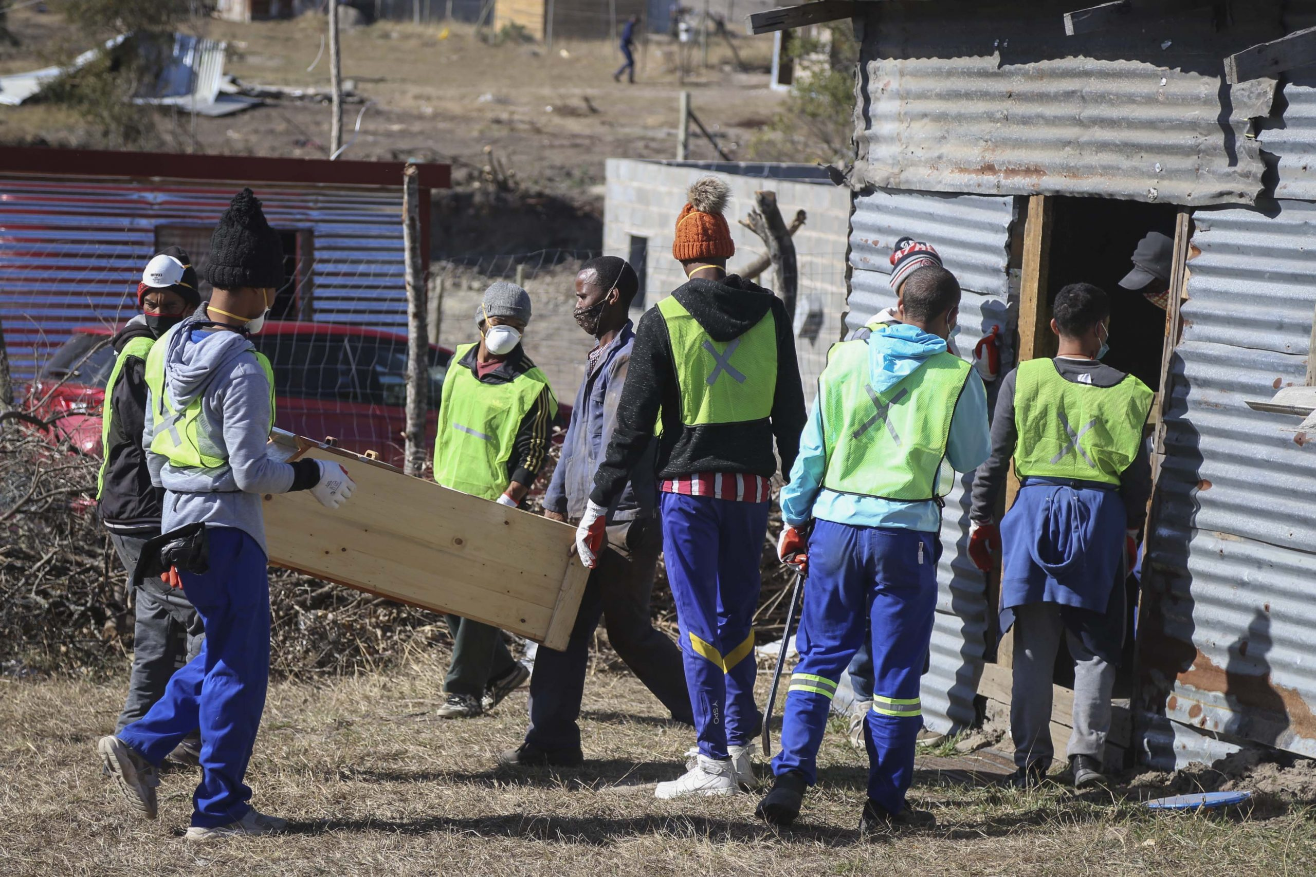 27 July 2020: Buffalo City Metro Municipality workers and a resident carry out benches from a structure used as the Zion Christian Church.