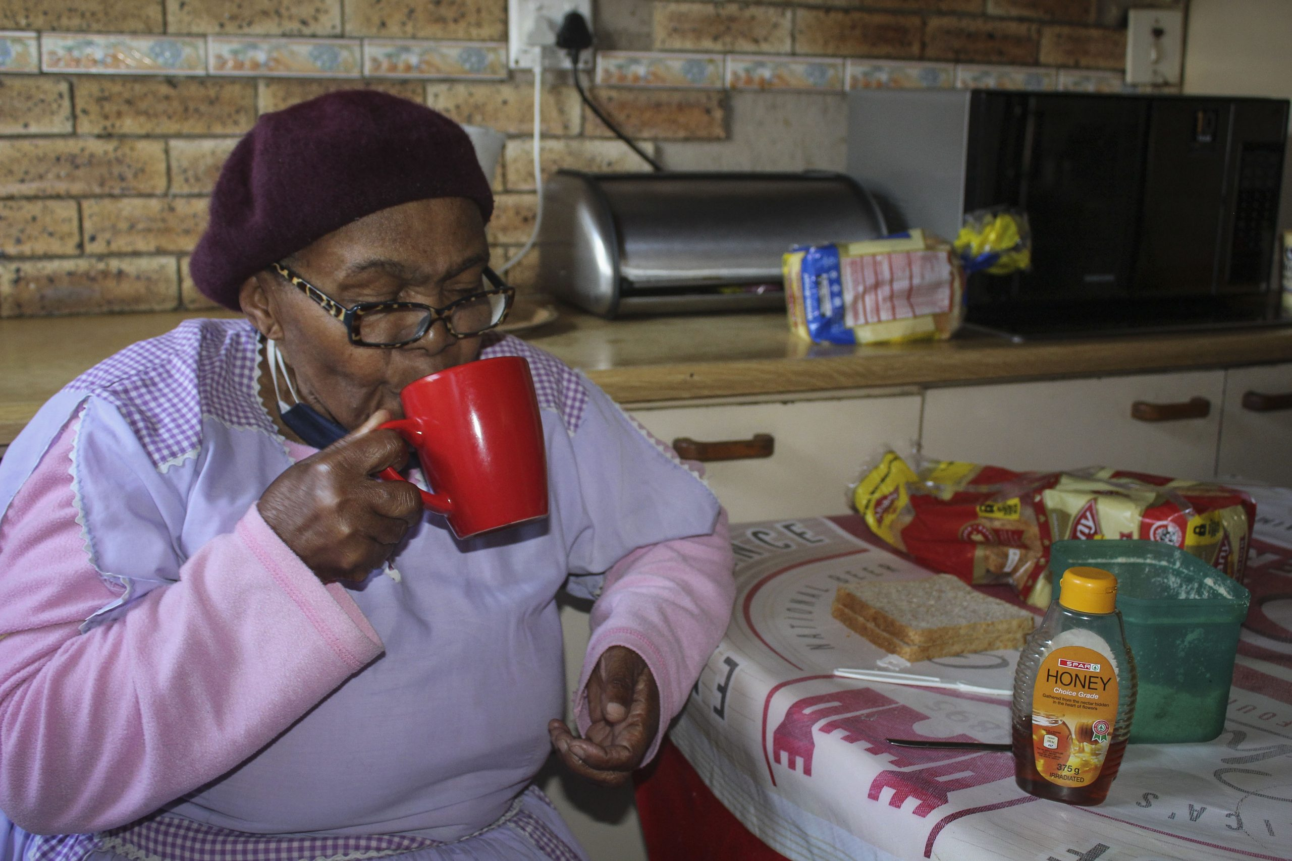 28 July 2020: Winnie Ndlovu, 76, drinks hot water with honey, garlic and ginger to relieve her chest and throat. (Photograph by Tony Carnie)