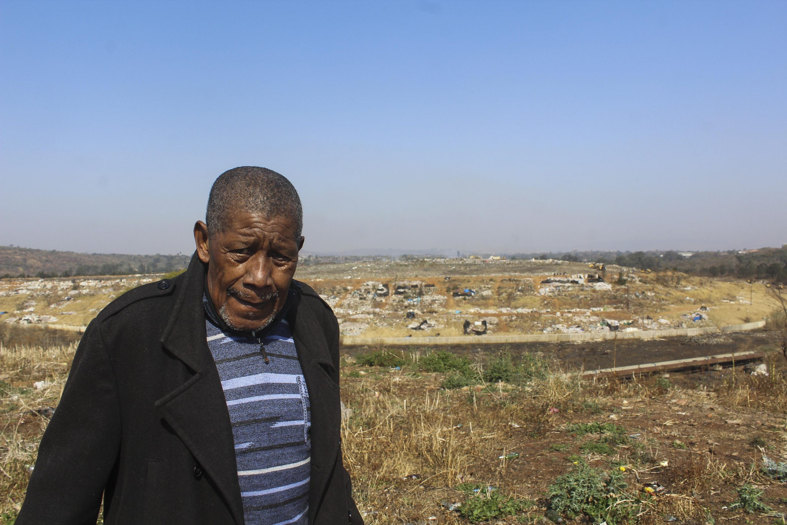 28 July 2020: Siphiwe Zondi, 71, pauses for breath while walking past the New England Road waste site. At least three elderly people died in their sleep in Sobantu at the end of July, when clouds of smoke from a fire at the dump blanketed the village. (Photograph by Tony Carnie)