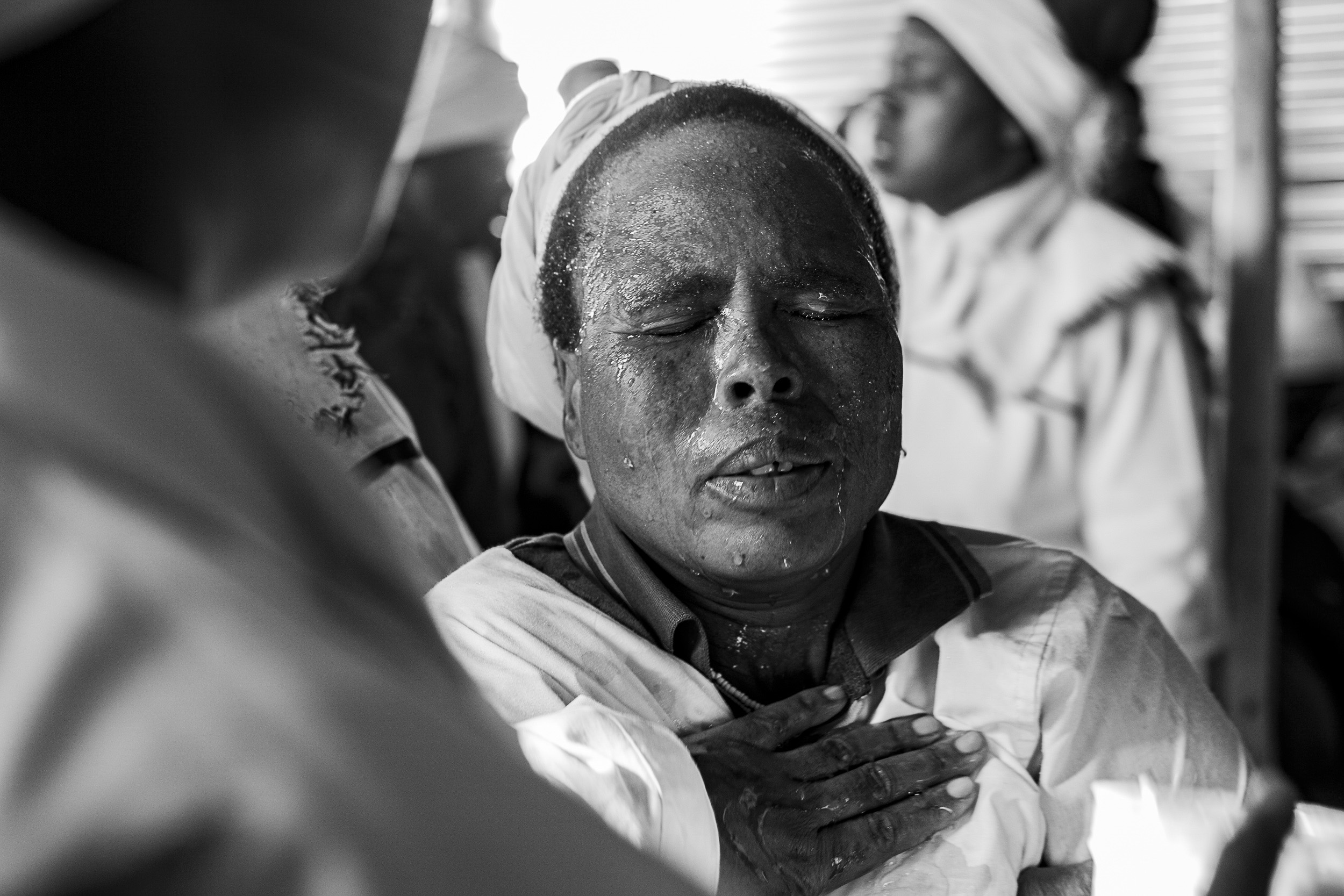 Undated: Ababekhwe Izandla II – Church members pray for a woman at Ukuphila KwamaKrestu church. Water and prayer ease pain after congregants have been in a trance-like state.