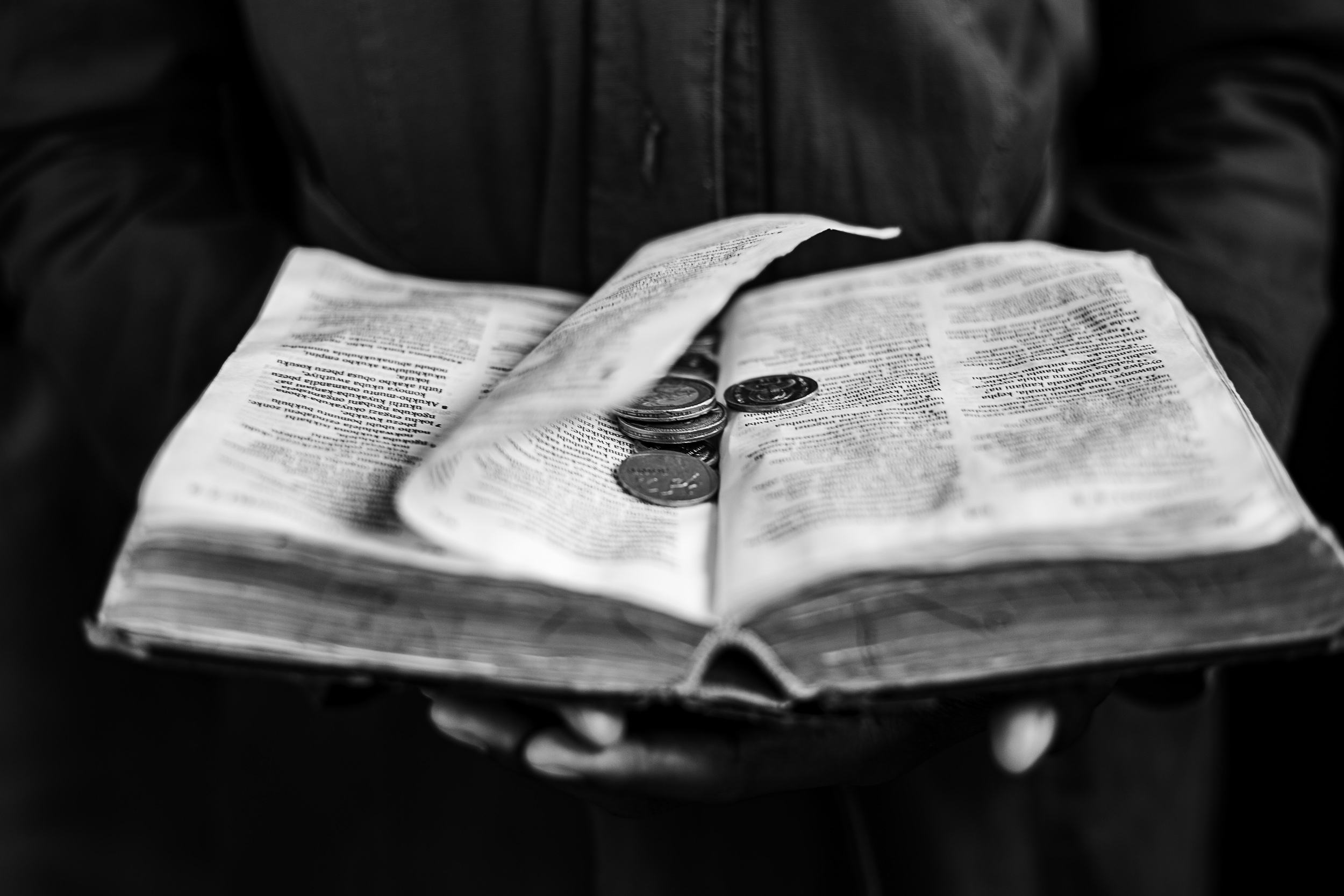 Undated: Okweshumi – Coins are placed on a Bible as tithes at the Ukuphila KwamaKrestu church.