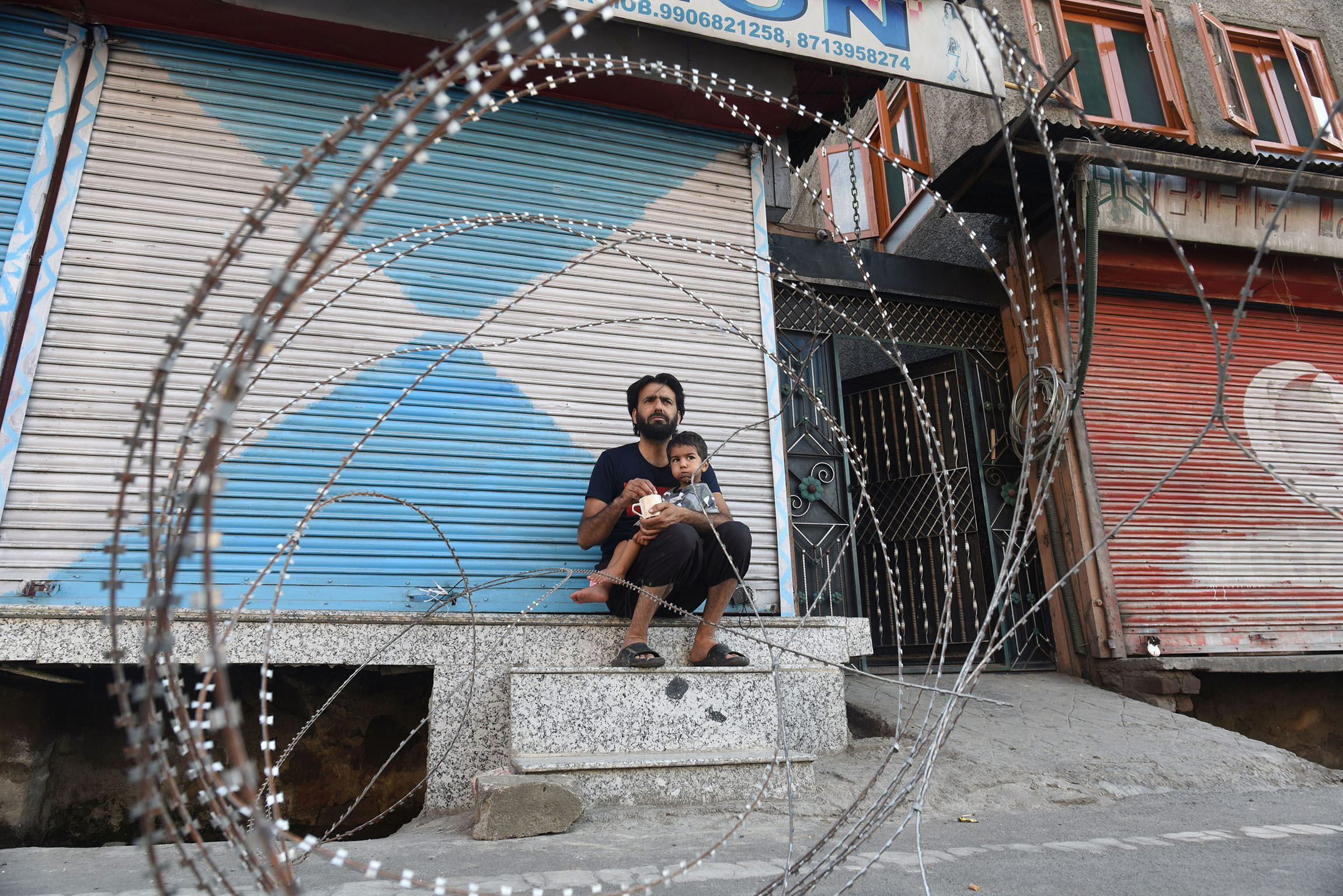 4 August 2020: A man feeds his child next to barbed wire installed to enforce a curfew in Srinagar, the largest city in Jammu and Kashmir. (Photograph by Waseem Andrabi/ Hindustan Times via Getty Images)
