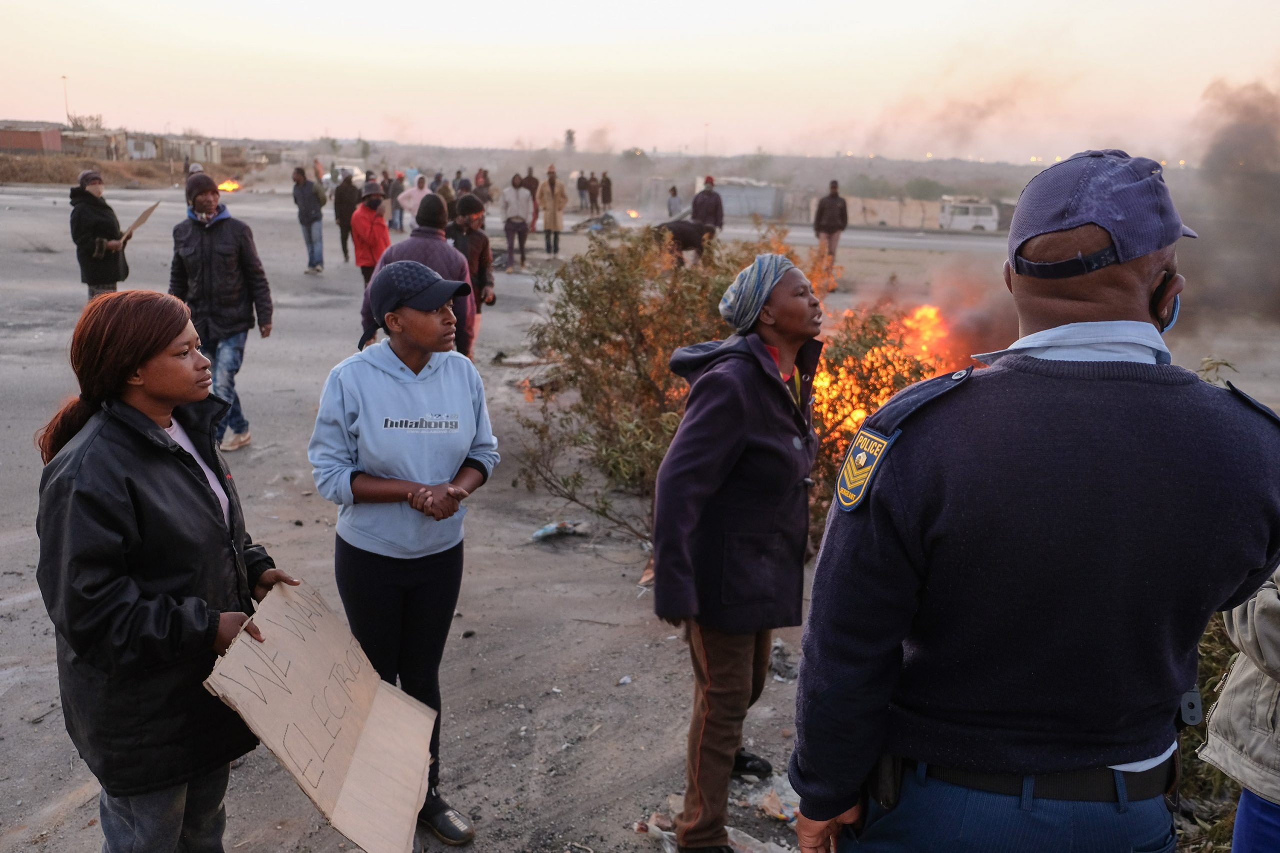 25 August 2020: Residents of the Doornkop shack settlement Tamara Bhengu* and Kelebogile and Constance Pogiso engage with the police before being fired at with rubber bullets and tear gas.