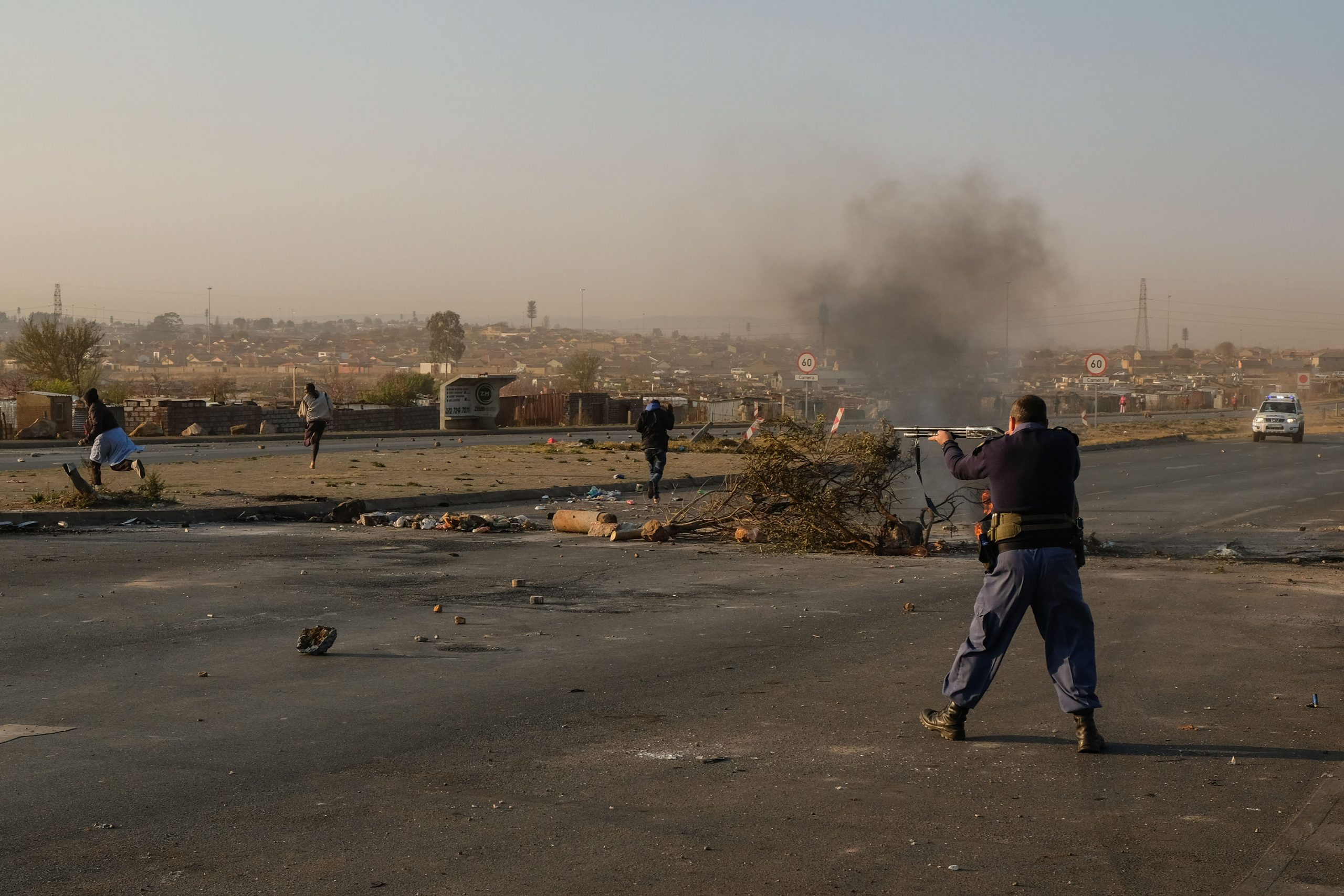 25 August 2020: A South African Police Service officer fires rubber bullets at Doornkop residents who were protesting against the lack of electricity in their shack settlement.