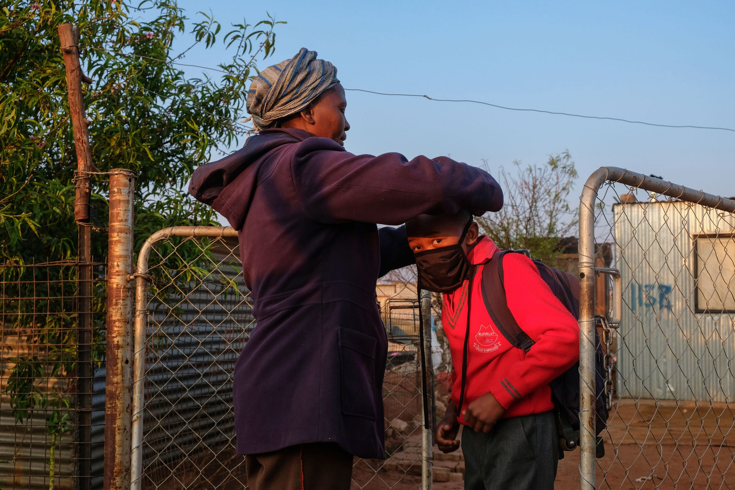 25 August 2020: Tamara Bhengu* takes a break from the protests to get her grandson ready for school. During the Covid-19 lockdown, children's homework was sent on WhatsApp, but without electricity Doornkop residents could not charge their cellphones.