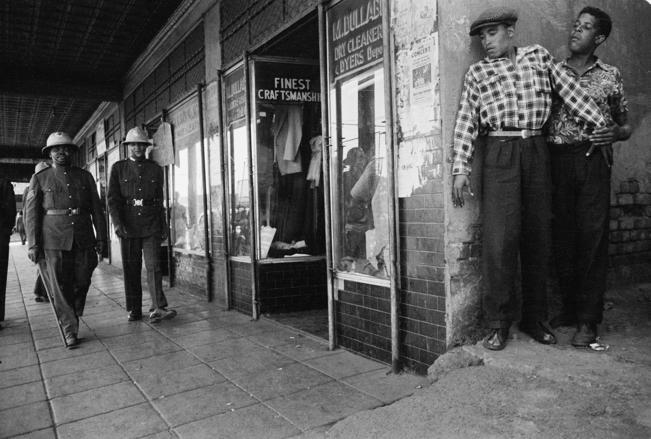 Circa 1955: Two men hide from the police in Johannesburg. If caught in the city without a pass, black persons were subject to arrest. (Photograph courtesy of the Jürgen Schadeberg estate)