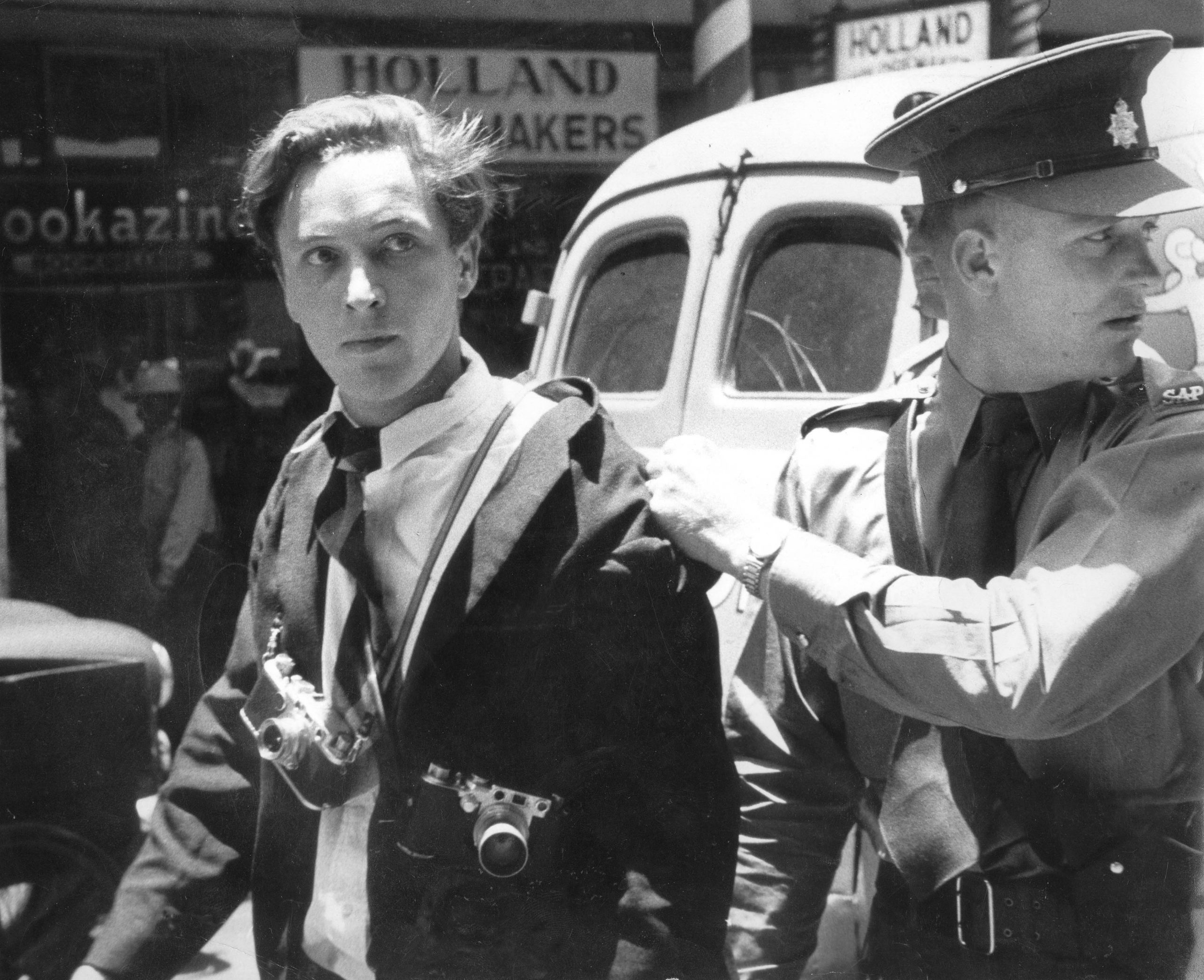 Circa 1958: Jürgen Schadeberg being arrested in Johannesburg for protecting one of his colleagues at Drum magazine. (Photograph by Ian Berry, courtesy of the Jürgen Schadeberg estate)