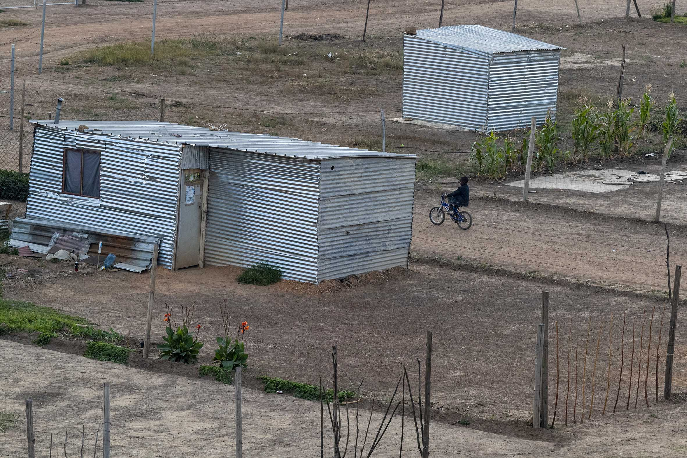 20 May 2021: A child rides his bike in Tjovitjo, a shack settlement established in 2017 near Orange Farm, south of Johannesburg. The dolomite beneath the settlement may dissolve and cause sinkholes if more permanent infrastrucure is brought in.